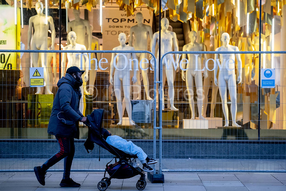 A man pushes a child in a buggy past unclothed mannequins which remain crowded together on the shop floor of fashion retailer Topshop on Oxford Street during the third lockdown of the Coronavirus pandemic, on 5th February 2021, in London, England. Asos struck a £295m deal to buy four brands from failed retail group Arcadia. The deal includes brands, Topshop, Topman, Miss Selfridge and HIIT brands, but not the shops, leaving thousands of jobs with uncertain futures.