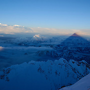 The shadow of Mount Everest stretches to the western horizon at sunrise from the 28,750 foot South Summit on the Southeast Ridge of Everest. Visible in the fireground is the serrated ridge of Nuptse leading down to the Western Cwm.