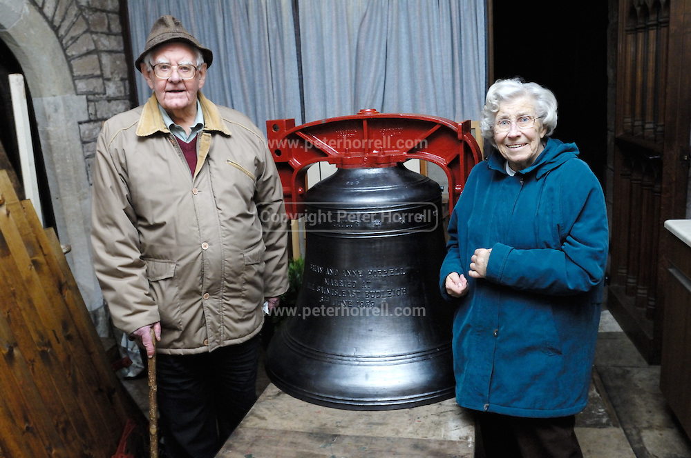 """UK, November 24 2014: Anne and Brian Horrell stand next to the new tenor bell that will be installed at All Saints East Budleigh church. The inscription on the bell states """"Anne and Brian Horrell married at All Saints East Budleigh 6th June 1959"""" . Copyright 2014 Peter Horrell."""