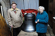 "UK, November 24 2014: Anne and Brian Horrell stand next to the new tenor bell that will be installed at All Saints East Budleigh church. The inscription on the bell states ""Anne and Brian Horrell married at All Saints East Budleigh 6th June 1959"" . Copyright 2014 Peter Horrell."