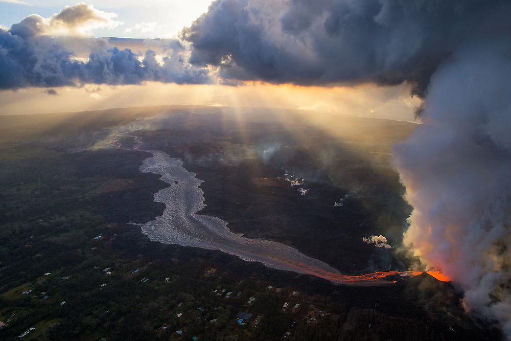 Kilauea's east rift zone: Crepuscular rays beam through puffy cumulus clouds over the eruption zone, creating quite an amazing scene, as fissure 8 continues to issue a tremendous amount of lava in the lower right.