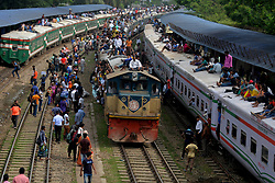June 14, 2018 - Dhaka, Bangladesh - People sit on the roof of train carriages as they head to their homes to celebrate Eid al-Fitr from Dhaka, Bangladesh. As the Eid al-Fitr festival knocking at the door, the long-distance bus stations, ferry terminals and train stations in Bangladesh capital Dhaka see overflowing with tens of thousands of home-bound passengers.  (Credit Image: © Xinhua via ZUMA Wire)