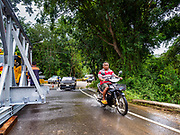 09 AUGUST 2018 - KAENG KRACHAN, PHETCHABURI, THAILAND:  A local resident rides his motorbike on a water covered rural road past a construction crew working on an emergency spillway for the Kaeng Krachan Dam. The Phetchaburi River flows from Kaeng Krachan Dam to the Gulf of Siam through several towns including Ban Lat, Phetchaburi (the capital of Phetchaburi province) and Ban Laem. Government officials have warned residents of those towns that their towns will flood because the reservoir behind the dam is approaching capacity. Ban Lat and Phetchaburi could be flooded for several weeks. Residents of Ban Laem have been warned that their community could be inundated for over a month. Dams in Kanchanaburi province, west of Phetchaburi, are also approaching capacity and flooding is also expected in that area.  PHOTO BY JACK KURTZ