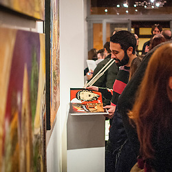 """A guest takes a look at one of the books done by an artist at an art opening in the gallery """"untitled"""" BCN."""