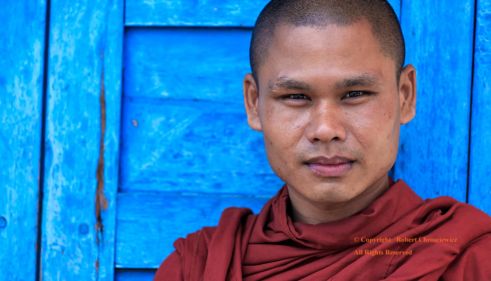 Sincere Monk , Blue Door: A sincere Buddhist monk poses in front of the blue door of his residence, Wat Toul Tompong, Phnom Penh, Cambodia.