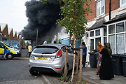 Local people gather to witness a massive scale fire at a plastics factory at Tyseley Industrial Estate on 10th August 2020 in Birmingham, United Kingdom. The blaze, which could be seen from miles away sent a vast and harmful plume of black smoke up into the air near residential homes and businesses in the area.  Roads were blocked off to all traffic as some 100 members of the fire service tackled the difficult fire.
