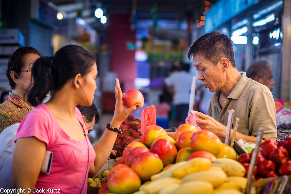 18 DECEMBER 2012 - SINGAPORE, SINGAPORE: A woman buys apples from a fruit vendor in Tekka Market in the Little India section of Singapore. PHOTO BY JACK KURTZ