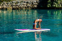 Standup paddleboard yoga class in the lagoon, Four Seasons Resort Bora Bora, French Polynesia.