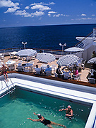 Tourists at sea onboard MV Minerva cruise ship Swan Hellenic holiday cruises swimming pool and deck 1997