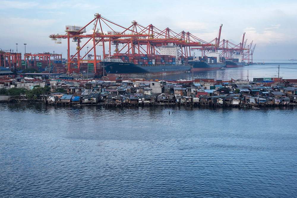 Slum housing sits adjacent to a commercial dock where three container ships are docked in Manila, Philippines