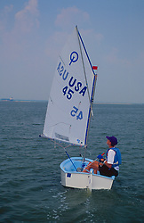 Stock photo of a boy sailing his boat on the water