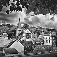 The gothic Notre Dame Church and other buildings are nestled into the hillside landscape of downtown Bougival, France.  Aspect Ratio 1w x 1h