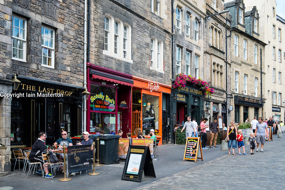 View of pubs and cafes along historic street in Grassmarket district of Edinburgh , Scotland, United Kingdom