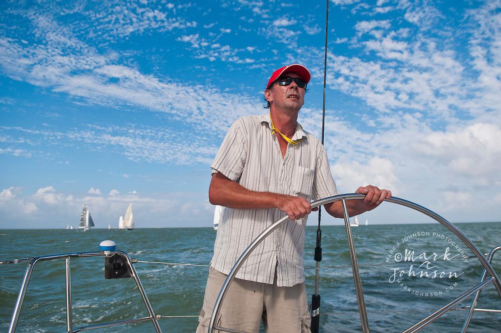 Sailboat Captain steering while sailing on Moreton Bay, Queensland, Australia