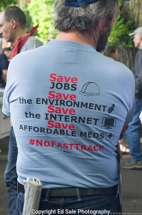 A protester at a 2015 May Day rally in Portland, Oregon wears a t-shirt that wants to save jobs, the enivronment, the Internet, affordable medications, and opposing FastTrack legislation.