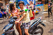 "13 APRIL 2013 - BANGKOK, THAILAND:  A man and his daughter wide a motor scooter through a water fight on Khao San Road, which is Bangkok's ""backpacker"" district, during Songkran celebrations in the Thai capital. Songkran is celebrated in Thailand as the traditional New Year's Day from 13 to 16 April. The date of the festival was originally set by astrological calculation, but it is now fixed. If the days fall on a weekend, the missed days are taken on the weekdays immediately following. Songkran is in the hottest time of the year in Thailand, at the end of the dry season and provides an excuse for people to cool off in friendly water fights that take place throughout the country. Songkran has been a national holiday since 1940, when Thailand moved the first day of the year to January 1.   PHOTO BY JACK KURTZ"