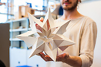 A final-year furniture design student shows off a model design.