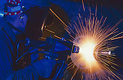 """A worker welds with a an electric arc welder as he joins stainless steel components. - To license this image, click on the shopping cart below - -- Determine pricing and license this image, simply by clicking """"Add To Cart"""" below --"""