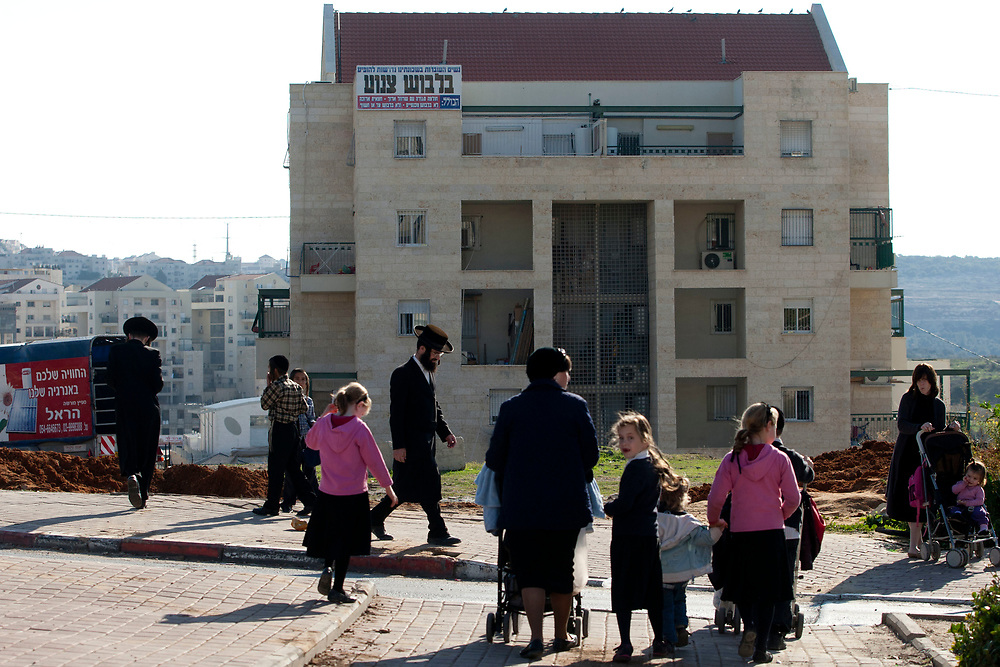 Ultra-Orthodox Jews walk down a street as a sign cautioning women to dress modestly hangs on a building in Beit Shemesh, Israel, on December 28, 2011.