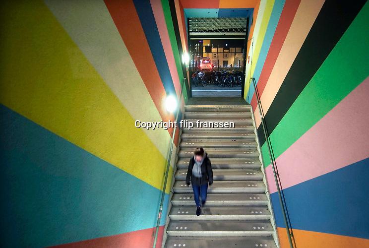 Nederland, Nijmegen, 30-11-2019Onder het poppodium Doornroosje is een fietsenstalling. Hij is een gratis, Openbare fietsenstalling naast het station. Ook de bewoners van de studentenflats boven de poptempel kunnen er hun fietsen kwijt. Je kunt al fietsend een plaats, plek, uitzoeken. Het kleurrijke ontwerp is van kunstenaar Jan van der Hoef. Bij de uitgang hangte een rijtijdenbord van de ns met de vetrektijden van de treinen. Avond, donker,nacht, avondfoto .Foto: Flip Franssen