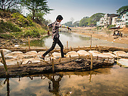 """01 MARCH 2014 - MAE SOT, TAK, THAILAND: A Burmese boy crosses a temporary footbridge to a boat landing in the Moie River in Mae Sot. Boats from Myawaddy, Myanmar (the buildings in the background are in Myawaddy) drop and pick up passengers for the short trip across the river. Mae Sot, on the Thai-Myanmar (Burma) border, has a very large population of Burmese migrants. Some are refugees who left Myanmar to escape civil unrest and political persecution, others are """"economic refugees"""" who came to Thailand looking for work and better opportunities.    PHOTO BY JACK KURTZ"""