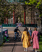 Summer dresses for the hot weather but the bandstand is shut because it is a focal point for meeting - A sunny day and people are out in reasonable numbers, on Clapham Common SW London, to get their daily exercise. But in this area the fears of teh police dont seem to have been realised as teh numbers are less than yesterday. The 'lockdown' continues for the Coronavirus (Covid 19) outbreak in London.