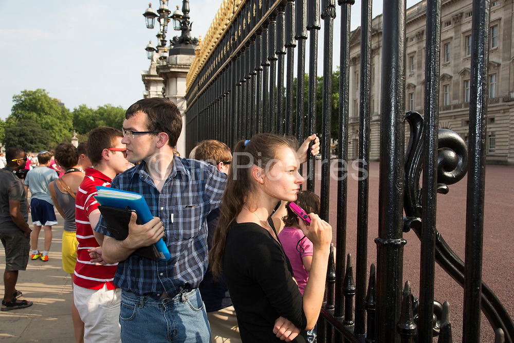 London, UK. Monday 22nd July 2013. Tourists outside Buckingham Palace awaiting news on the day that Kate Middleton Duchess of Cambridge was taken into hospital after going into labour.