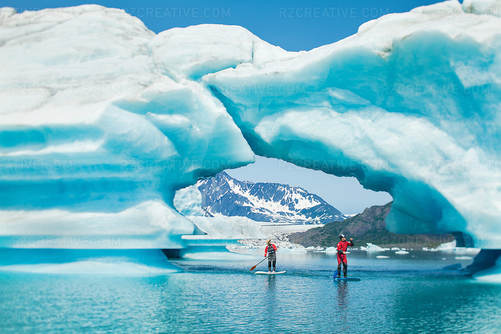 Paddlers Pam Sousa (left) and Dave Shively (right) paddle through a large archway of ice at Bear Glacier, Alaska. Photo by Robert Zaleski/rzcreative.com