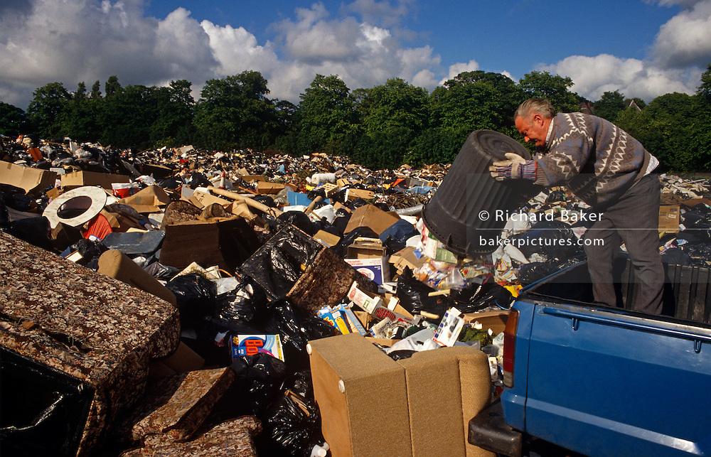 Standing on the back of his utility vehicle, a man empties the contents of his dustbin onto a growing pile of rubbish in a recreation park in the otherwise  affluent Allerton area of Liverpool, Merseyside, England, during the Merseyside dustmans' strike of 1991. Adding to this mountain of refuse, the 'Scouse' man (someone from Liverpool) is seen surrounded by black binliners and items from domestic homes which have been allocated this public space to become a temporary landfill. The industrial action aginst the local authority - over pay and working conditions  - was a health problem for Liverpool's population during the summer of 1991 when streets filled with rubbish. Vermin like rats ran around and public city parks such as this were filled with every kind of refuse and garbage.