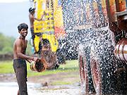 Washing trucks in the rain, Mangalore; Karnataka, India
