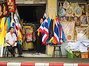 18 OCTOBER 2016 - BANGKOK, THAILAND: Shopkeepers sell Thai flags, the yellow flag of Bhumibol Adulyadej, the King of Thailand, and portraits of the late King. Thai King Bhumibol Adulyadej died Oct. 13, 2016. He was 88. His death came after a period of failing health. Bhumibol Adulyadej was born in Cambridge, MA, on 5 December 1927. He was the ninth monarch of Thailand from the Chakri Dynasty and is also known as Rama IX. He became King on June 9, 1946 and served as King of Thailand for 70 years, 126 days. He was, at the time of his death, the world's longest-serving head of state and the longest-reigning monarch in Thai history.     PHOTO BY JACK KURTZ