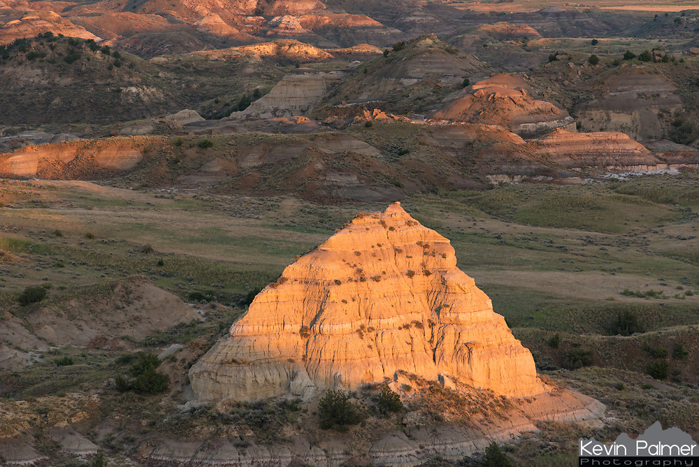 The last sunlight of the day shines on rock formations in the Terry Badlands.