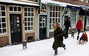Een vrouw rent met een meisje op de slee door de Lichte Gaard in Utrecht