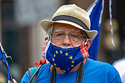 """An anti-Brexit campaigner wearing a surgical face protective mask resembling EU's Flag holds up a banner outside Parliament in Central London on Wednesday, July 22, 2020.<br /> The British government - under the Conservative Party leadership of David Cameron, Theresa May and Boris Johnson - failed to conduct serious assessments of Russian attempts to interfere with British elections, including the 2016 Brexit referendum, according to the long-delayed """"Russia Report"""" released on Tuesday. (VXP Photo/ Vudi Xhymshiti)"""