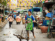 24 FEBRUARY 2016 - BANGKOK, THAILAND:  A porter walks through Pak Khlong Talat in Bangkok. Bangkok government officials announced this week that vendors in Pak Khlong Talat, Bangkok's well known flower market, don't have to move out on February 28. City officials are trying to clear Bangkok's congested sidewalks and they've cracked down on sidewalk vendors. Several popular sidewalk markets have been closed in recent months and the sidewalk vendors at the flower market had been told they would be evicted at the end of the month but after meeting with vendors and other stake holders city officials relented and said vendors could remain but under stricter guidelines regarding sales hours. The flower market is one of the best known markets in Bangkok and has become a popular tourist destination.       PHOTO BY JACK KURTZ