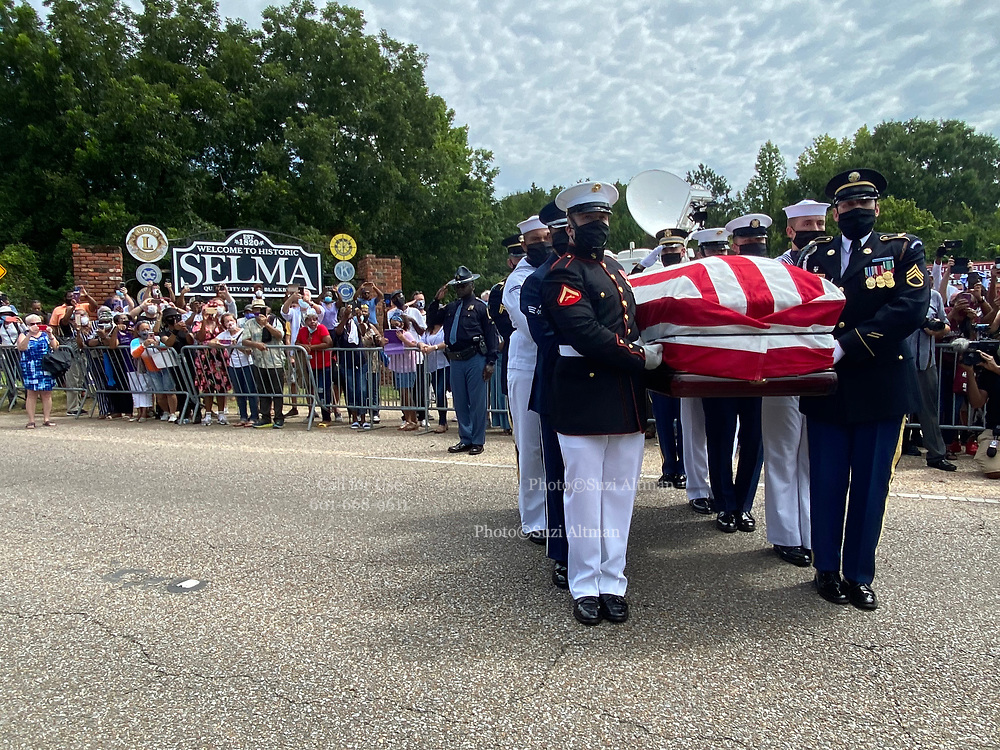 7/26/2020 SELMA/Alabama - The United States honor Guard carry the casket of Civil Rights Icon and Congressmen John Lewis from the horse the horse drawn carriage that just crossed the Edmund Pettus Bridge for the last time into the casket to head to the State Capitol, where he will lay in state.. A horse drawn carriage from Watkins Funeral Home in Atlanta leads the flag draped casket of Civil Rights icon and Congressman John Lewis over the Edmund Pettus Bridge for the last time.The rose petals represent the blood shed from Bloody Sunday in 1965 where Lewis was beaten by police and ended up with a  fractured skull. On the anniversary of President Lyndon Johnson signing the Voting Rights Act, Congressman John Lewis's casket is pulled by a horse drawn carriage  across the Edmund Pettus Bridge in Selma for the last time. The casket is headed to the State Capitol in Montgomery where he will lay in state and then will head to Washington DC and then to his final resting place in Atlanta Georgia.  Photo© Suzi Altman