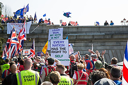 London, UK. 29th March, 2019. Pro-Brexit activists from Leave Means Leave pass Remain supporters o a bridge during a march from Fulham to a rally in Parliament Square in Westminster on the final leg of the March to Leave on the day on which the UK was originally to have left the European Union. The March to Leave was organised by Leave Means Leave, with assistance from Nigel Farage, as a peaceful protest 'to demonstrate the depth and breadth of popular discontent with the way Brexit has been handled' by the Government.