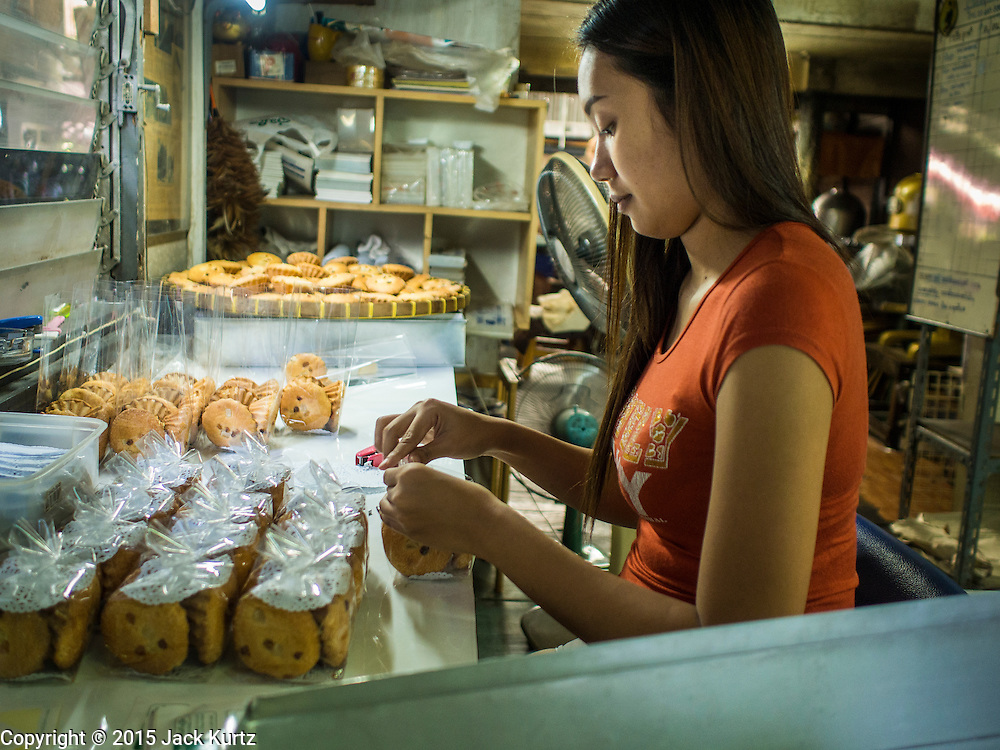 """06 FEBRUARY 2015 - BANGKOK, THAILAND: A worker at Thanusingha Bakery packages freshly baked traditional Thai Catholic desert cakes. The cakes are called """"Kanom Farang Kudeejeen"""" or """"Chinese Monk Candy."""" The tradition of baking the cakes, about the size of a cupcake or muffin, started in Siam (now Thailand) in the 17th century AD when Portuguese Catholic priests accompanied Portuguese soldiers who assisted the Siamese in their wars with Burma. Several hundred Siamese (Thai) Buddhists converted to Catholicism and started baking the cakes. When the Siamese Empire in Ayutthaya was sacked by the Burmese the Portuguese and Thai Catholics fled to Thonburi, in what is now Bangkok. The Portuguese established a Catholic church near the new Siamese capital. Now just three families bake the cakes, using a recipe that is 400 years old and contains eggs, wheat flour, sugar, water and raisins. The same family has been baking the cakes at the Thanusingha Bakery, near Santa Cruz Church, for more than five generations. There are still a large number of Thai Catholics living in the neighborhood around the church.        PHOTO BY JACK KURTZ"""