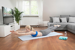 Young woman exercising on exercise mat in living room, Bavaria, Germany