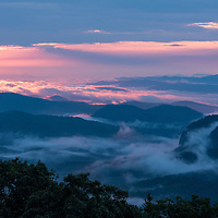 A glowing pink sunrise looking towards Looking Glass Rock from the Looking Glass Overlook on the Blue Ridge Parkway in the Pisgah National Forest southwest of Asheville, North Carolina.