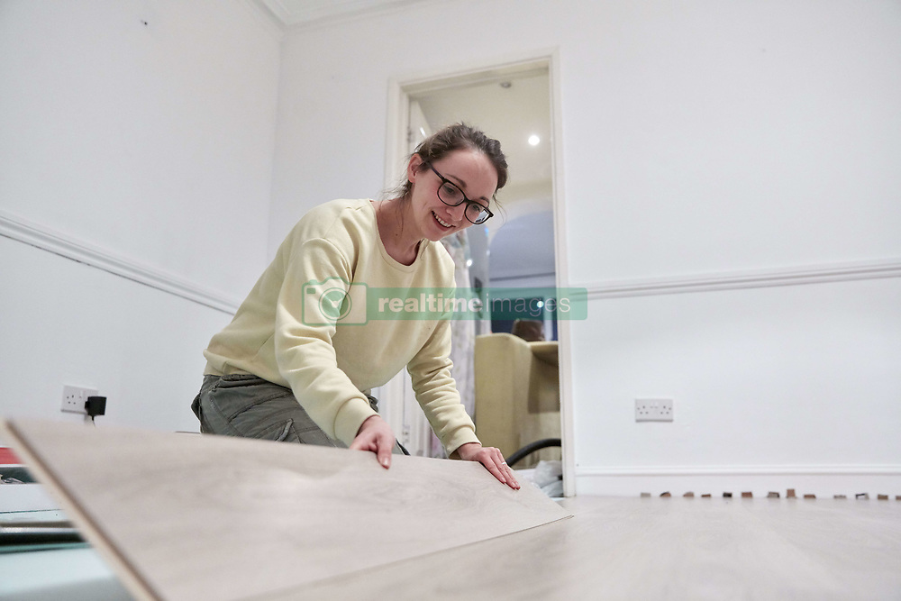 February 14, 2018 - Woman fitting new wooden floor board (Credit Image: © Mint Images via ZUMA Wire)