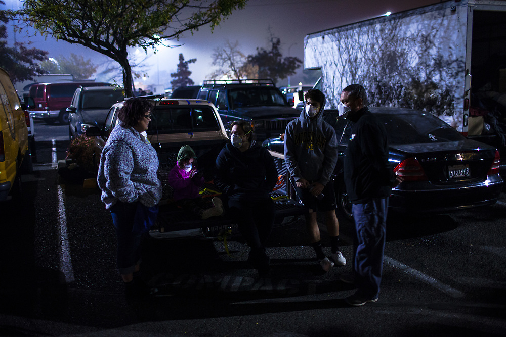 Auburn resident Evangeline Del Bono, 42, left, speaks to Paradise residents Isabelle Marc, 5, her mother Elizabeth Marc, 42, her brother Francis Marc, 17, and father Paul Marc, 50, as they gather in a Walmart parking lot, after the Marc family was displaced by the Camp Fire, in Chico, California, Friday, November 16, 2018.