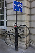 A bicycle has been locked high up on a City of London street sign post where arrows point up and down, the coincidence of a visual pun - in the heart of the capital's financial district. The authorities recommend locking up a bike in specified areas, making sure they're secured with a substantial D-lock. The bike is a Specialized road bike of a single-gear variety.