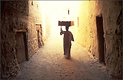 Man carries grate through the covered passages of 600 year old, mud brick, village of El quasr in Dakhla oasis. Egypt