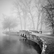 """This is an open edition print. Canvas prints have a 2 inch black border so it can be gallery wrapped. The print is made using pigmented inks on museum-grade canvas or watercolor paper. Each print also gets a light coating of lacquer protective spray. Each print is hand signed by Brian DeWolf.  The little stone bridge at Island Park in Geneva, Illinois seems like it came from a fantacy when surrounded by fog. It was built during the Great Depression when workers were greatful to be sweating out a day's pay. Aspect ratio is 1""""w x 1""""h."""