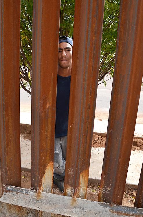 "A man in Agua Prieta, Sonora, Mexico, who identified himself as, ""Jesus"", looks through the boder wall in to Douglas Arizona, USA."