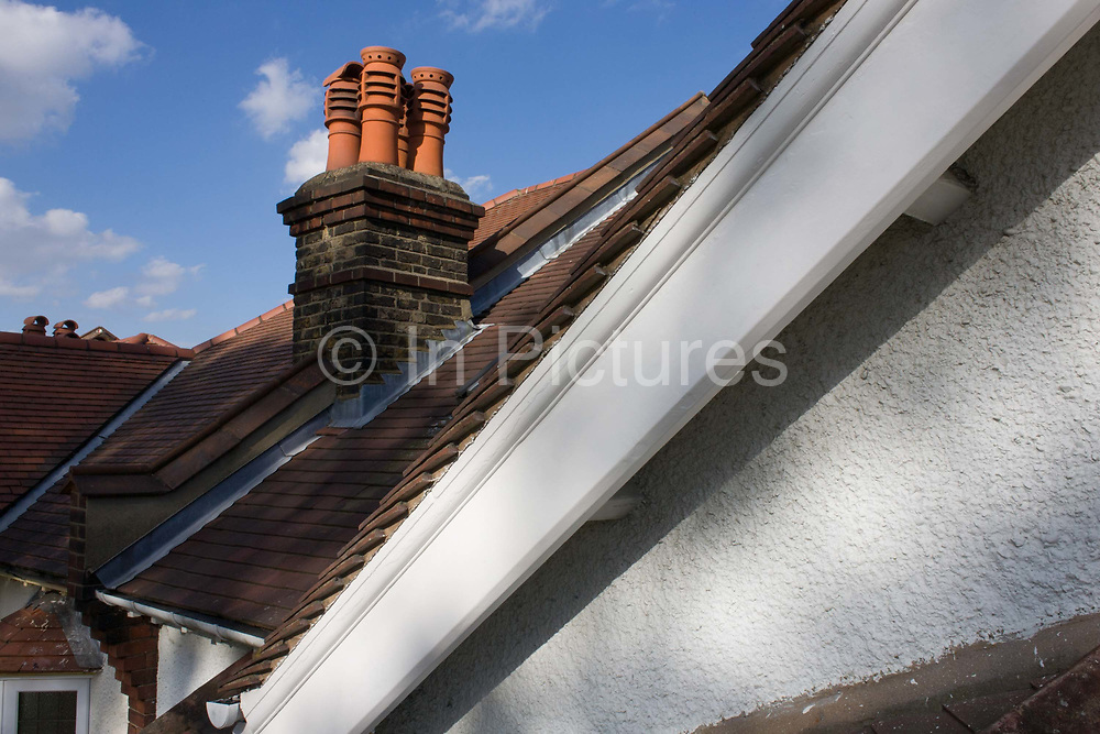 Rooftop view of a suburban Edwardian semi-detached house in south London. We are high up at roof level on a sunny afternoon in the borough of Lambeth where  middle-class houses were built around the time of the first world war and whose building workforce probably did not return. The fireground has the prominent diagonal of the gable, recently painted by the home owner