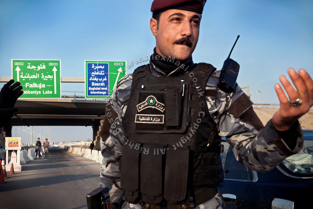 An Iraqi Police officer is guarding traffic at the main checkpoint to the city of Fallujah, Iraq, on Highway N.10. (Baghdad-Fallujah-Ramadi)
