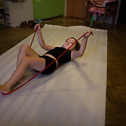 CAPTION: Ksenya's daughter Yana practises her gymnastics routine inside the family's room in a St Petersburg communal apartment. NAME MUST BE CHANGED. LOCATION: St Petersburg, Russia. INDIVIDUAL(S) PHOTOGRAPHED: Yana Shpunt.