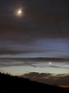 Salisbury Mills, New York - The cresent moon and the planet Venus, at lower right, shine through the clouds above Schunnemunck Mountain at twilight on Nov. 27, 2011.